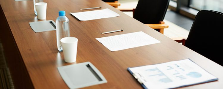 Drinking water in bottles, papers and pens on conference table prepared for business educational event