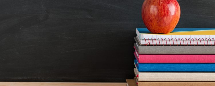 Red apple on top of a stack of school books with a blackboard in the background
