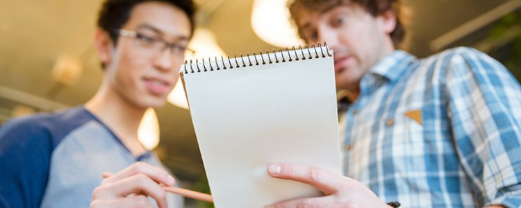 Student showing his notes to a friend